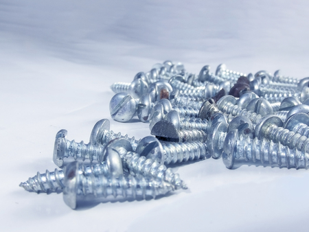 hard component: Bunch of screws in macro in the white background.