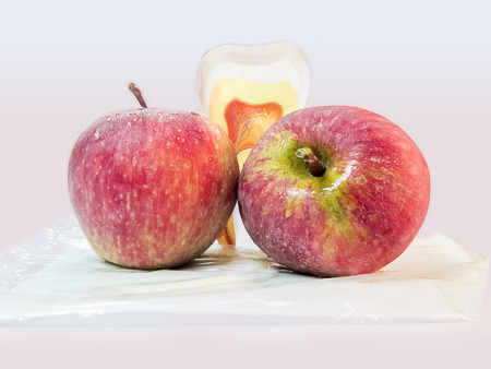 Two Apples and an artficial tooth.Apple good for dental health.An apple  a day keep the doctor away.Dental health. Stock Photo