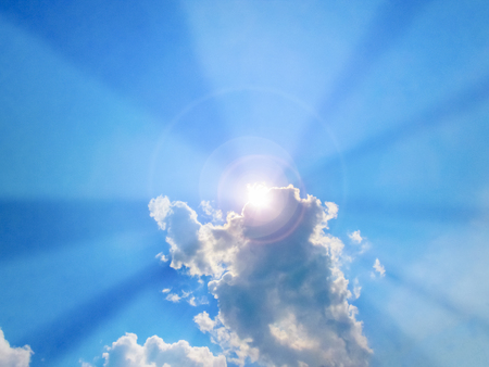 midday: Sun beam coming out of the clouds in midday in the blue sky Stock Photo