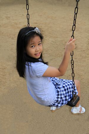 Portrait of cute asian girl swinging photo