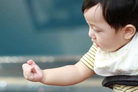 Cute baby boy Blick auf seine Hand Lizenzfreie Bilder
