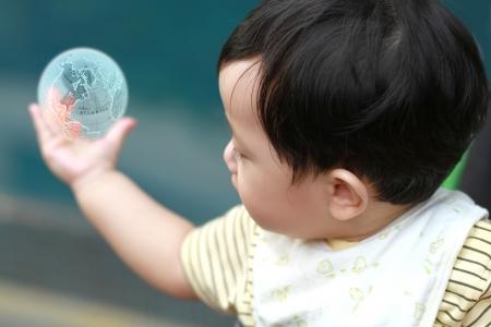 Cute baby boy Blick auf der Erde auf seiner Hand Lizenzfreie Bilder