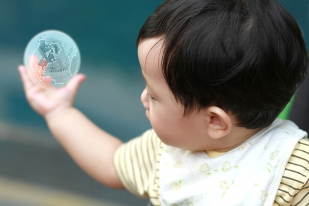 global thinking: Cute baby boy looking at earth on his hand