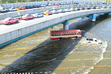 decades: BANGKOK, THAILAND - NOVEMBER 13: Cars park in row on a bridge to avoid flooding during the worst flooding in decades in Bangkok, Thailand on November 13, 2011.