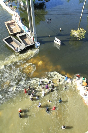 BANGKOK, THAILAND - NOVEMBER 13: Water barrier are destroyed by group of people to open the water flow to the opposite during the worst flooding in decades in Bangkok, Thailand on November 13, 2011.