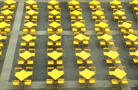 Row of yellow tables and chairs photo