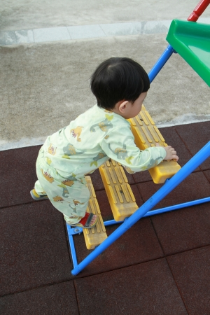 Baby boy climbing steps of slider Stock Photo