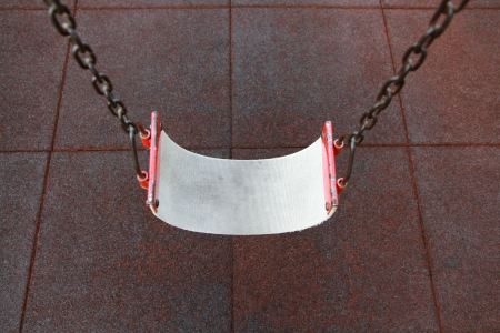 Empty swing set on red floor background  photo
