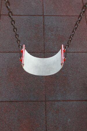 Empty swing set on red floor background  photo