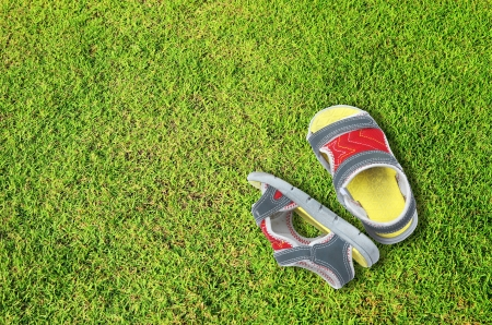 Old children shoes on green grass floor photo