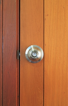 Stainless steel door knob on wooden door  photo