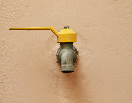 Yellow handle water tap on rough pink wall  photo