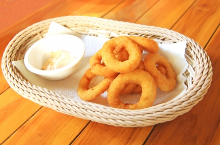 Fried onion rings on absorbent paper in white basket photo