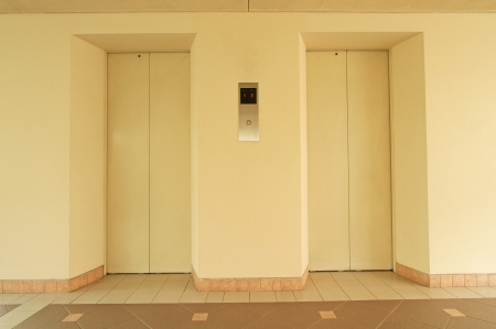 Two elevator doors and decorative tiled floor photo