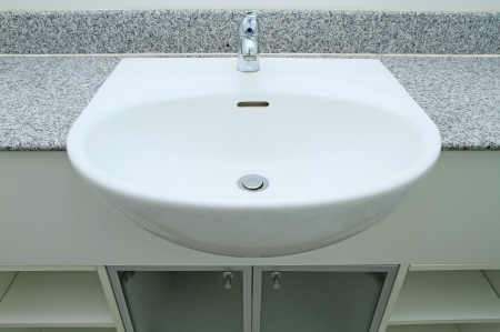 Ceramic handbasin on granite countertop  photo