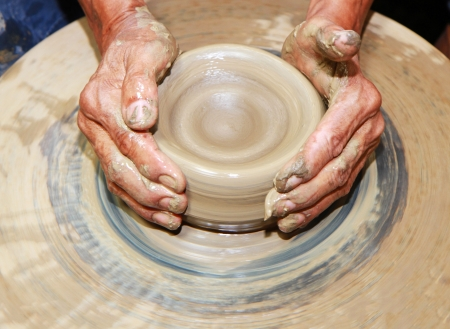 Close-up of hands making pottery on pottery wheel photo