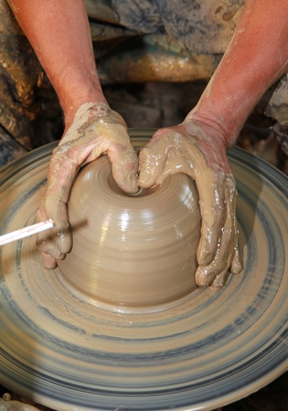 Close-up of hands making pottery on pottery wheel