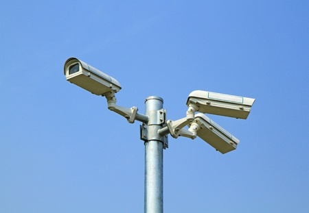 Three security cameras against blue sky  photo