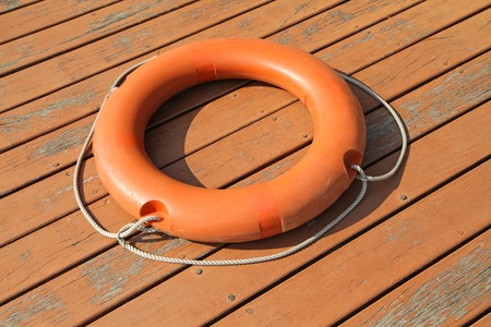 An orange lifebuoy ring on wooden floor Stock Photo - 18737256