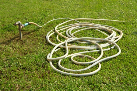 Rubber tube with aged faucet on green grass field  photo