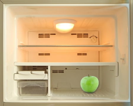 Green apple in an empty refrigerator photo