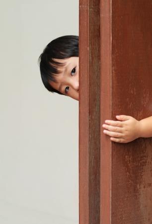 Jonge jongen achter een houten wand