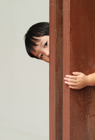 Young boy behind wooden wall