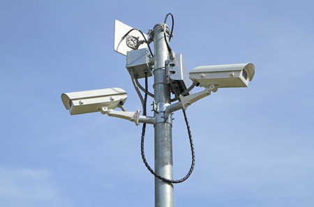 Two security cameras against blue sky photo