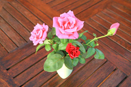 Beautiful bouquet of red and pink roses in white vase on wooden background  photo