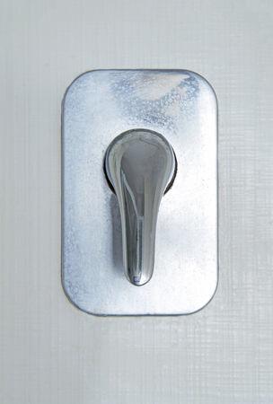 Shower valve on white tiled wall photo