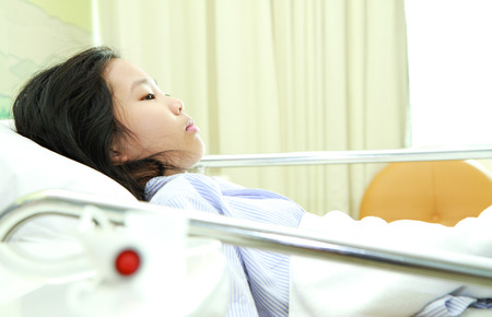 Young asian woman patient in hospital bed photo