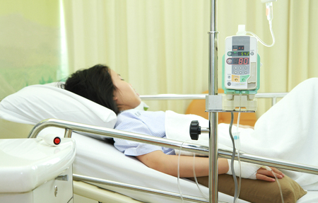 Woman patient in hospital bed with medical infusion drip tool photo