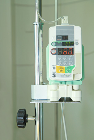 Medical infusion machine located on stand in hospital room photo