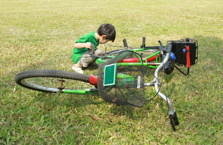 Asian boy looking on fallen big bicycle in green grass field photo