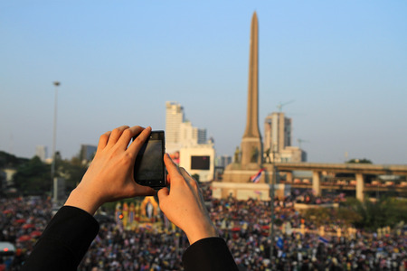 BANGKOK,THAILAND- DECEMBER 22  A protester uses a smartphone to capture an anti-government corruption protest at Victory monument on December, 2013 in Bangkok, Thailand