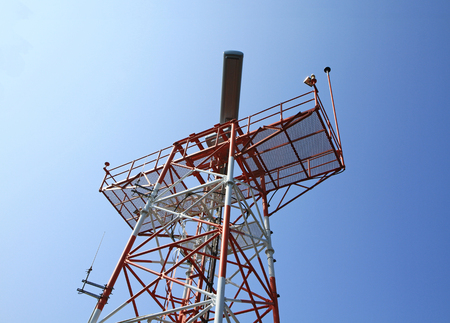 Red Color radar tower against blue sky background photo