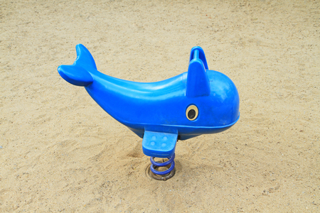Spring blue dolphin on sand floor playground photo