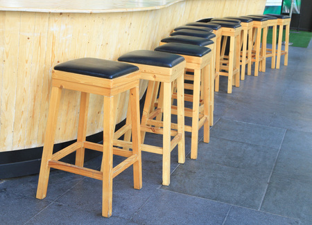 Lined up of wooden bar stools photo