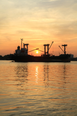 slipway: Silhouette of cargo ship in the river on twilight time