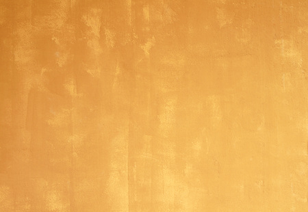 orange color: Yellow cement wall textured background.