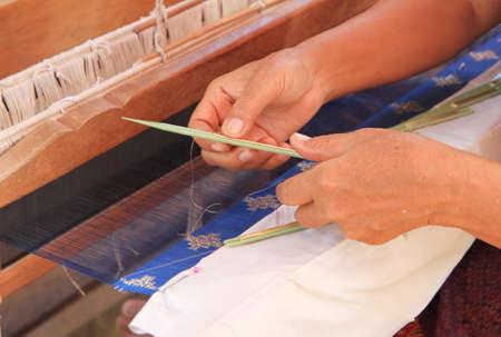 loom: Woman hand weaving pattern on loom