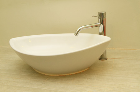 handbasin: Ceramic handbasin on with faucet on countertop