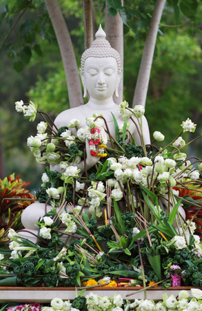 puja: Buddhism worship with offering flowers and garland to buddha statue on Magha Puja, Asalha Puja and Visakha Puja Day in Thailand