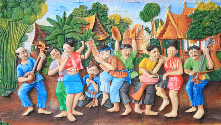 thai dance: Stone carving and painting of traditional Thai musical instrument and Thai dance on temple wall