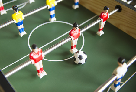 Close up image of table socker game and players