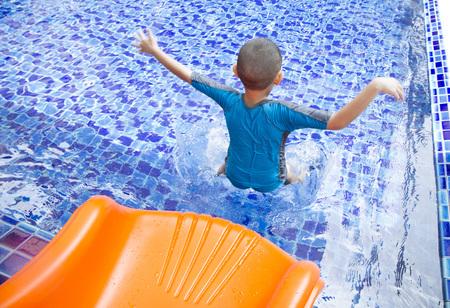 Asian boy play pool slider into blue pool
