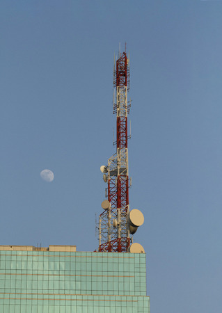 Telecommunication tower with moon on blue sky