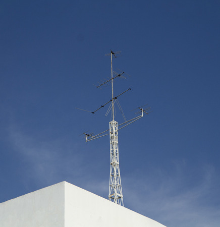 TV antennas on white building with blue sky background
