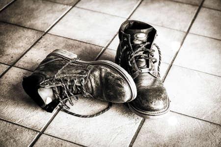 tiredness: Black boots on a tiled floor