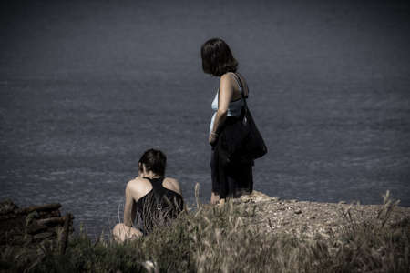 crouches: Two in black dressed women at the seashore. The Both are to be seen only from the back. Their position is pensive. The stones in the foreground and the light strengthen the gravity of grief ago.